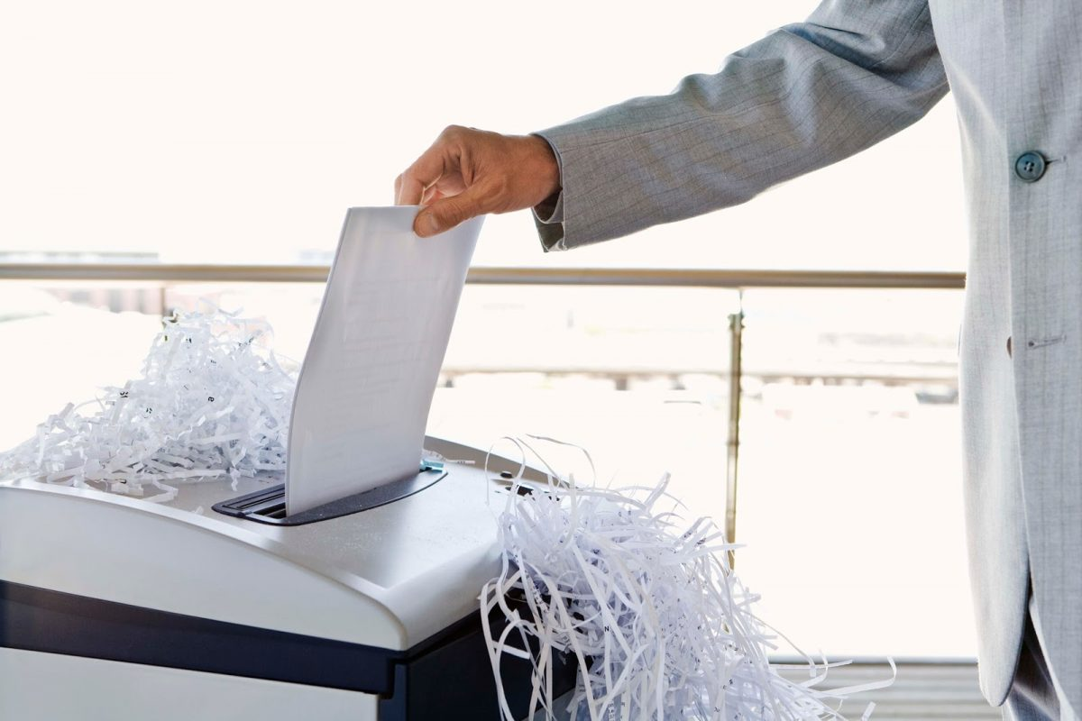 Businessman with overflowing paper shredder