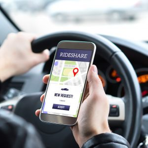Ride share driver in car using the rideshare app in mobile phone