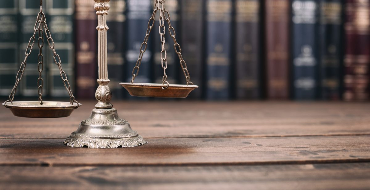 Scales of Justice and Law books on a wooden background.